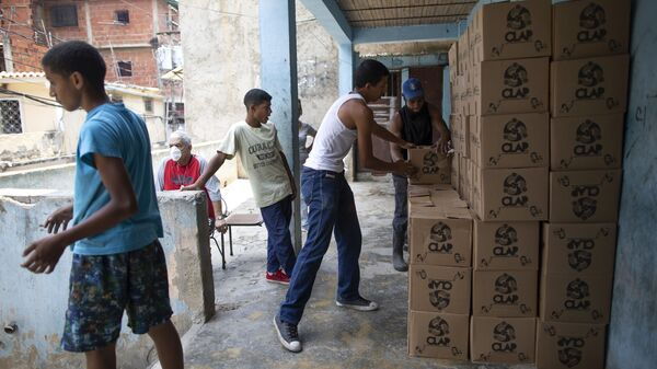 Residents help to unload and stack boxes of basic food staples, such as pasta, sugar and flour, provided by a government food assistance program, in Caracas' slum of Petare, Venezuela, Thursday, April 30, 2020.  - Sputnik International