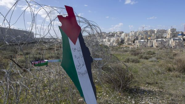 Placard with the colors of the Palestinian flags in front of Israeli barrier. - Sputnik International