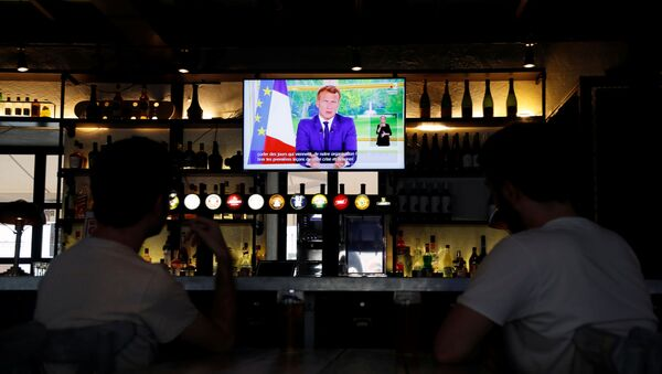 French President Emmanuel Macron is seen on a television screen in a pub while he addresses the nation - Sputnik International