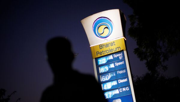 FILE PHOTO: A Bharat Petroleum oil pump station displays the price of unleaded petrol (0.89$) and Diesel (0.66$) as a pedestrian walks past in New Delhi, India, February 3, 2016. - Sputnik International