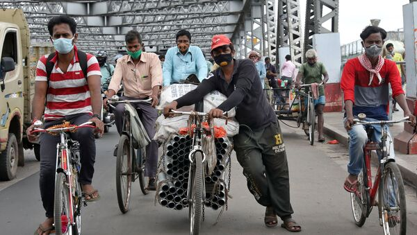 People wearing protective face masks ride their bicycles on Howrah bridge, after authorities eased lockdown restrictions that were imposed to slow the spread of the coronavirus disease (COVID-19), in Kolkata, India, June 12, 2020 - Sputnik International