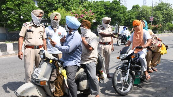 Police personnel check commuters after strict lockdown norms for weekends and public holidays were imposed as a preventive measure against the COVID-19 coronavirus, in Amritsar on June 14, 2020 - Sputnik International