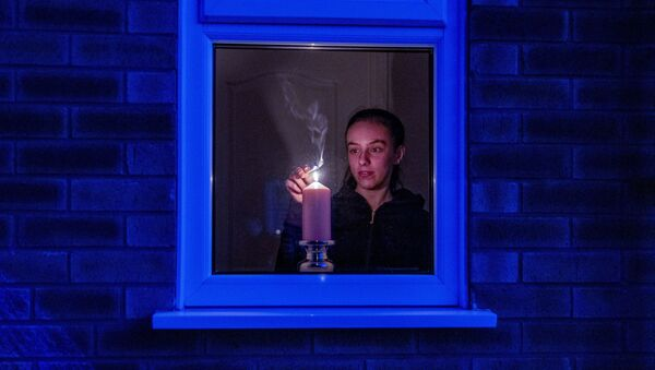 Woman lights a candle in the window of a home in Liverpool, England, after the Queen stressed the importance of maintaining the coronavirus lockdown during the Easter Bank Holiday weekend as she delivered what is believed to be her first Easter address, Saturday, April 11, 2020 - Sputnik International