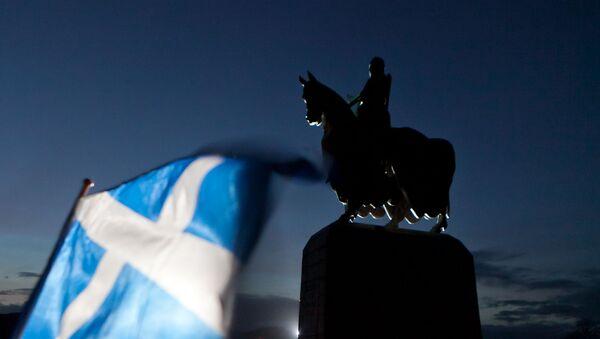 A Scottish Saltire flag blows in the wind near the statue of Scottish King Robert the Bruce, at Bannockburn, Scotland, Thursday, Jan. 12, 2012 - Sputnik International
