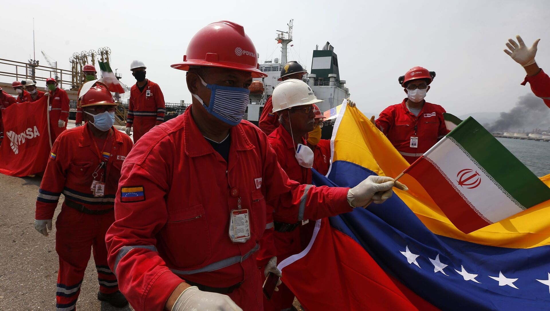 A Venezuelan oil worker holding a small Iranian flag attends a ceremony for the arrival of Iranian oil tanker Fortune at the El Palito refinery near Puerto Cabello, Venezuela, Monday, May 25, 2020 - Sputnik International, 1920, 24.06.2021