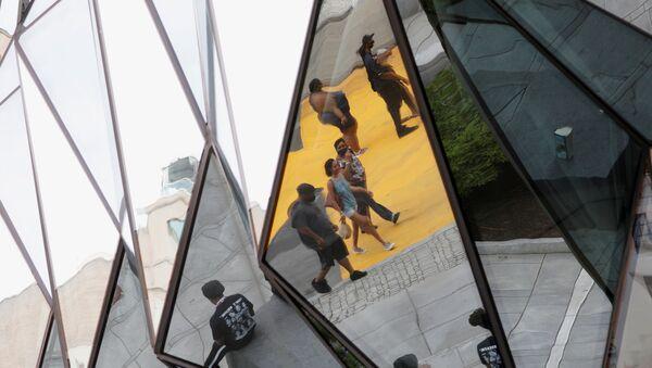 Pedestrians are seen reflected in a building mirror along Black Lives Matter Plaza near the White House in Washington, D.C. June 16, 2020.  - Sputnik International