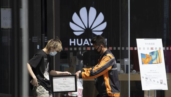 A delivery man hands over drinks near a Huawei retail store in Beijing on Monday, May 18, 2020 - Sputnik International