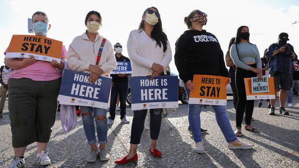 People hold signs as they take part in a rally for Justice Everywhere to celebrate the U.S. Supreme Court's ruling to disallow the rescinding of the Deferred Action for Childhood Arrivals (DACA) program, in San Diego, California, U.S., June 18, 2020. - Sputnik International