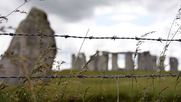 The Stonehenge stone circle is seen through a barbed wire, where official Summer Solstice celebrations were cancelled due to the spread of the coronavirus disease (COVID-19), near Amesbury, Britain June 20, 2020 - Sputnik International