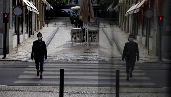 A woman wearing a protective mask walks, amid the coronavirus disease (COVID-19) outbreak, in downtown Lisbon, Portugal, May 14, 2020 - Sputnik International