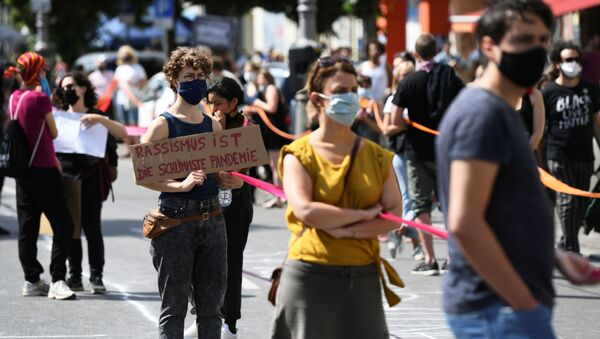 A person holds a banner reading Racism is the worst pandemic as participants of the so-called Indivisible demonstration form a human chain in support of the Black Lives Matter movement and to protest against the lockdown following the coronavirus disease (COVID-19) outbreak, in Berlin, Germany, June 14, 2020.  - Sputnik International