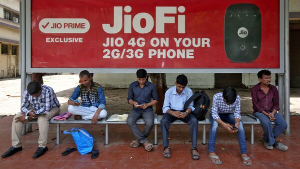 Commuters use their mobile phones as they wait at a bus stop with an advertisement of Reliance Industries' Jio telecoms unit, in Mumbai, India July 10, 2017 - Sputnik International