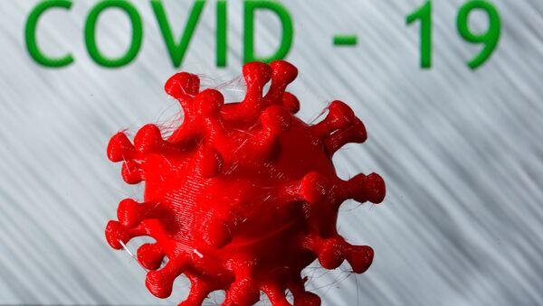 A 3D-printed coronavirus model is seen in front of the words coronavirus disease (Covid-19) on display in this illustration taken March 25, 2020. - Sputnik International
