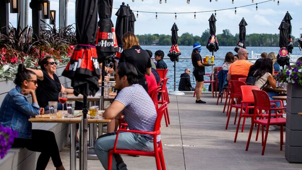 People enjoy drinks and food at Amsterdam Brewhouse's patio, as the provincial phase 2 of reopening from the coronavirus disease (COVID-19) restrictions begins in Toronto, Ontario, Canada June 24, 2020. - Sputnik International