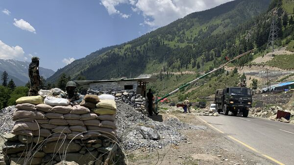 Indian paramilitary soldiers keep guard as Indian army convoy moves on the Srinagar-Ladakh highway at Gagangeer, north-east of Srinagar, India, Thursday, June 18, 2020. - Sputnik International