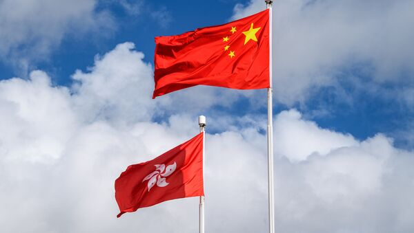 The Chinese (R) and Hong Kong (L) flags are seen hoisted at the end of a flag-raising ceremony to mark the 23rd anniversary of Hong Kong's handover from Britain in Hong Kong on July 1, 2020 - Sputnik International