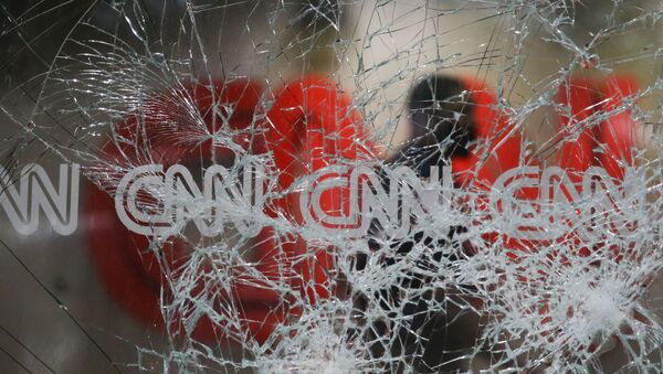 A security guard walks behind shattered glass at the CNN building at the CNN Center in the aftermath of a demonstration against police violence on Saturday, May 30, 2020, in Atlanta. - Sputnik International