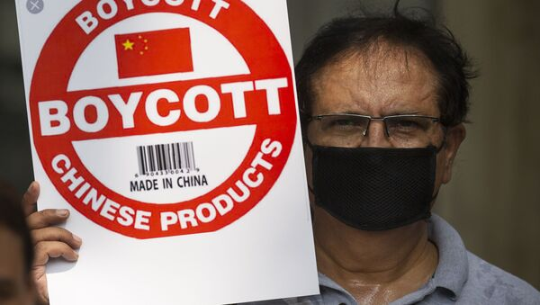An Indian journalist holds a placard calling for a boycott of Chinese products - Sputnik International