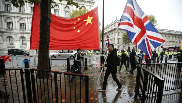 A supporter of Chinese President Xi Jinping carries a large British flag past the national flag of China outside Downing Street  where he is meeting the British Prime Minister David Cameron in London, Wednesday, Oct.  21, 2015 - Sputnik International