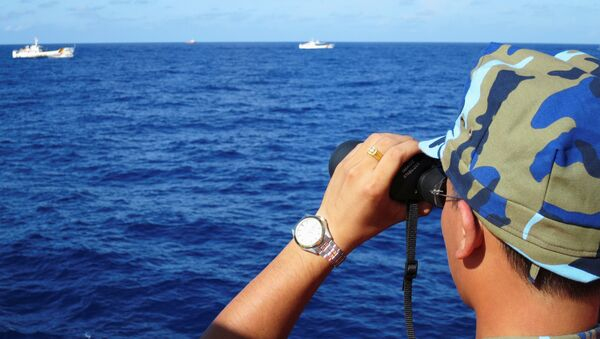 A crewman from the Vietnamese coastguard ship 8003 looks out at sea as Chinese coastguard vessels give chase to Vietnamese ships that came close to the Haiyang Shiyou 981, known in Vietnam as HD-981, oil rig in the South China Sea, July 15, 2014. - Sputnik International
