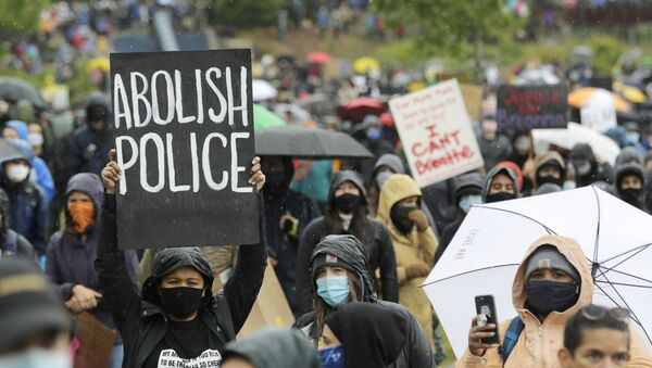 A protester holds a sign that reads Abolish Police during a Silent March against racial inequality and police brutality that was organized by Black Lives Matter Seattle-King County, Friday, 12 June 2020, in Seattle - Sputnik International