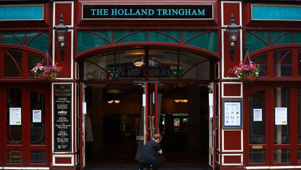 A staff member opens the doors of The Holland Tringham Wetherspoons pub - Sputnik International