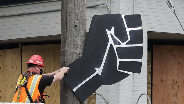 A worker removes a rendering of a clenched fist from a Seattle police precinct Wednesday, July 1, 2020, in Seattle, where streets had been blocked off in an area demonstrators had occupied for weeks. Seattle police showed up in force earlier in the day at the occupied protest zone, tore down demonstrators' tents and used bicycles to herd the protesters after the mayor ordered the area cleared following two fatal shootings in less than two weeks. The Capitol Hill Occupied Protest zone was set up near downtown following the death of George Floyd while in police custody in Minneapolis. - Sputnik International