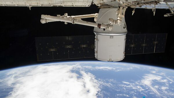 This NASA photo obtained 10 March 2020 shows the SpaceX Dragon resupply ship attached to the International Space Station's (ISS) Harmony module as both spacecraft soared 265 miles (426 km) above the Atlantic coast of Brazil on 9 March 2020. - Sputnik International