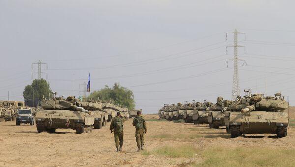 Israeli soldiers walk past tanks in a gathering point near Israel Gaza border, Friday, Oct. 19, 2018. - Sputnik International