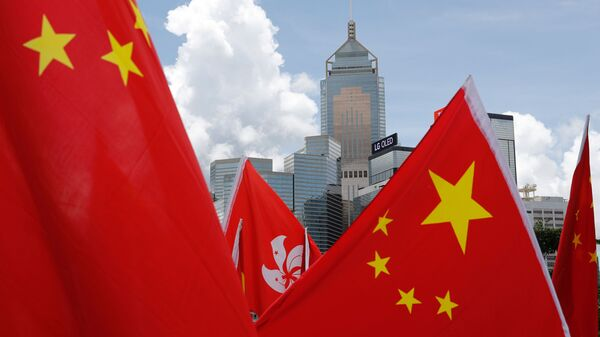 Buildings are seen above Hong Kong and Chinese flags, as pro-China supporters celebration after China's parliament passes national security law for Hong Kong, in Hong Kong, China June 30, 2020. REUTERS/Tyrone Siu - Sputnik International