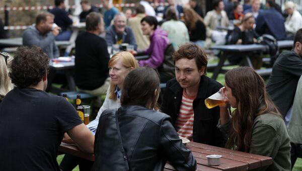 People drinking outside a pub in London on 4 July 2020 - Sputnik International