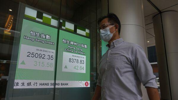 A man wearing a face mask walks past a bank electronic board showing the Hong Kong share index at Hong Kong Stock Exchange Tuesday, June 9, 2020. - Sputnik International