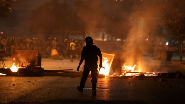 A member of the Lebanese riot police walks near burning fire during a protest against the fall in pound currency and mounting economic hardship, in Beirut, Lebanon June 12, 2020 - Sputnik International