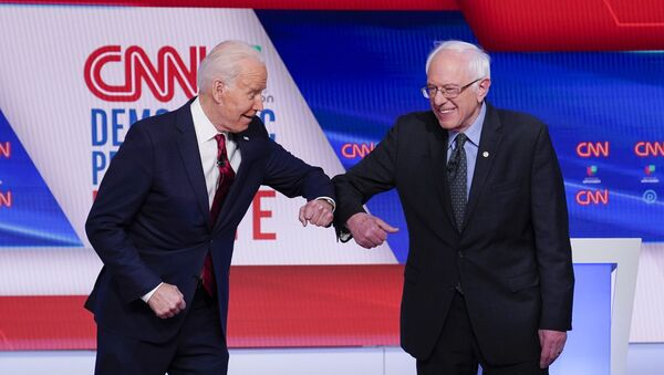 Former Vice President Joe Biden, left, and Sen. Bernie Sanders, I-Vt., right, greet one another before they participate in a Democratic presidential primary debate at CNN Studios in Washington, Sunday, March 15, 2020 - Sputnik International