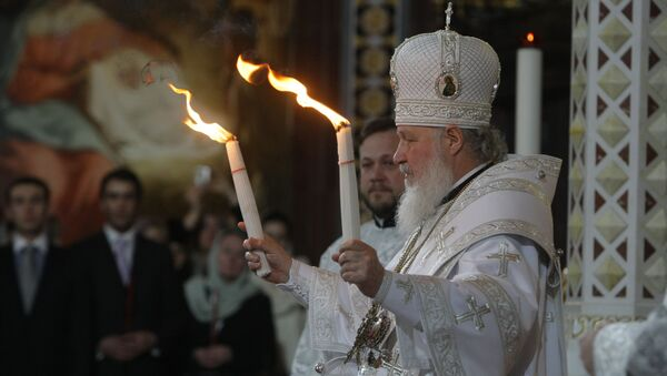 Patriarch Kirill of Moscow and All Russia handed the Holy Fire delivered from Jerusalem to all those thousands of faithful gathered at Moscow's Christ the Savior Cathedral on the Easter Night - Sputnik International