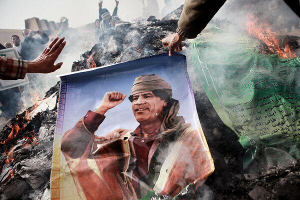 Rebel burns a poster depicting Libyan leader Muammar Gaddafi - Sputnik International