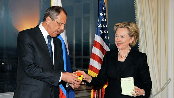 U.S. Secretary of State Hillary Clinton gives Russian Foreign Minister Sergei Lavrov the block with a red button marked reset in English and overload in Russian during a meeting in Geneva on March 6, 2009 - Sputnik International