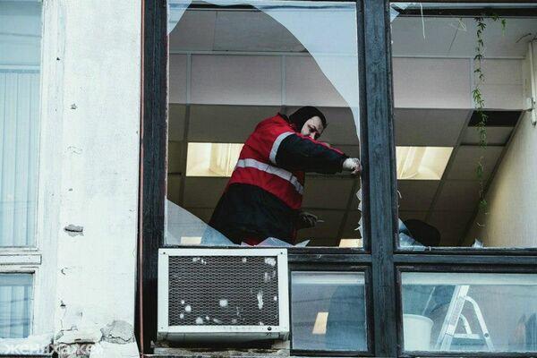A worker clears away glass from windows damaged by Friday's meteorite hits  in central Russia's Chelyabinsk Region - Sputnik International