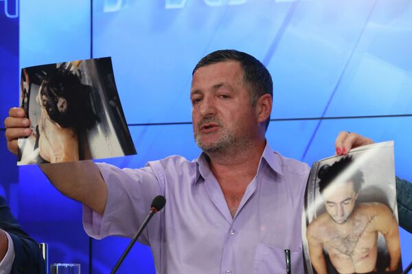 Abdulbaki Todashev showing photos of what he said was his son's bullet-riddled body, at a press conference in Moscow on May 30 - Sputnik International