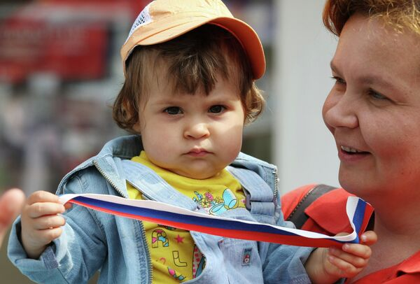 A woman with a child, who holds a ribbon having the colors of the Russian flag - Sputnik International