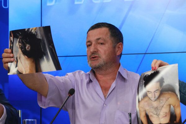 Abdulbaki Todashev, Ibraghim Todashev's father, holds up photos of his dead son at a press conference at the RIA Novosti headquarters in Moscow on May 30. - Sputnik International