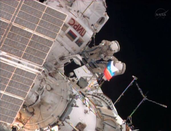 A cosmonaut unfurls a Russian flag outside the ISS during a spacewalk on Thursday to mark Russian Flag Day. - Sputnik International