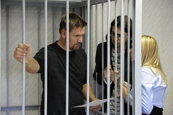 Greenpeace activist Anthony Perrett, charged with piracy, stands behind bars during his court hearing in Murmansk, Russia, on Sunday. - Sputnik International