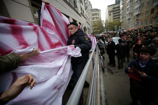 A police officer in a seeming tug-of-war with Mikhail Kosenko's supporters outside a Moscow court, Oct. 8, 2013. - Sputnik International