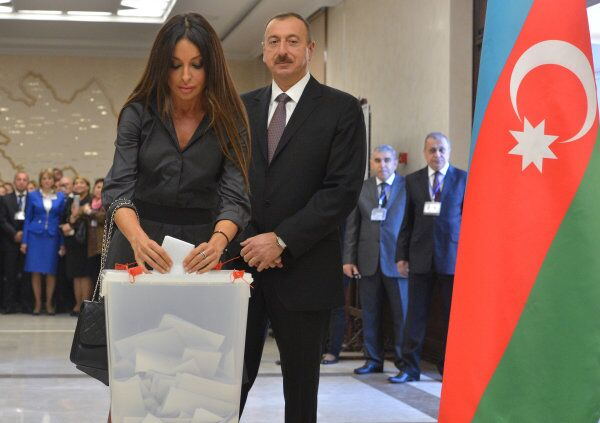 Incumbent Azerbaijani President Ilham Aliyev watches his wife, Mehriban, cast her vote for the presidential election at a polling station in Baku, the country's capital, on Wednesday. - Sputnik International