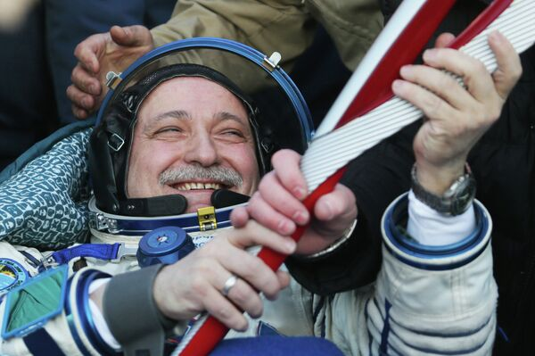 Russian cosmonaut Fyodor Yurchikhin with the Olympic torch in his hands after a capsule of the Soyuz TMA-09M spacecraft under his command lands in Kazakhstan. - Sputnik International