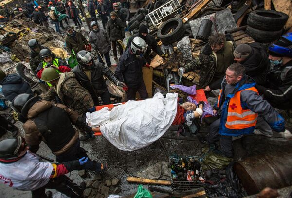 Protesters carry an injured comrade during a clash with riot police in Kiev - Sputnik International