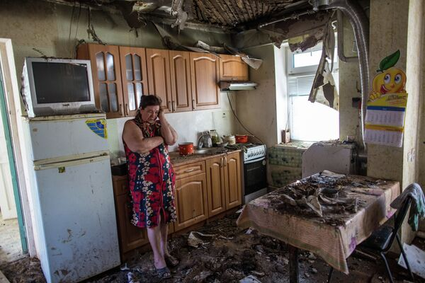 A woman in her house damaged during the night artillery attack conducted by Ukrainian troops on the outskirts of Slavyansk - Sputnik International