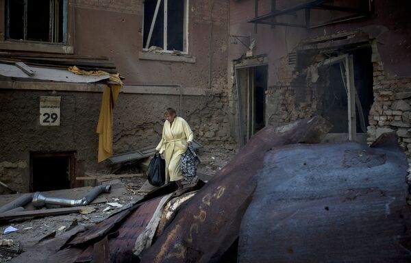 A woman is seen outside a residential building destroyed in an artillery attack by the Ukrainian army on Luhansk - Sputnik International