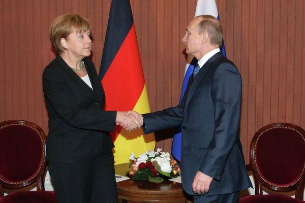 Vladimir Putin, shaking hands with Angela Merkel during his visit to Deauville, France. - Sputnik International